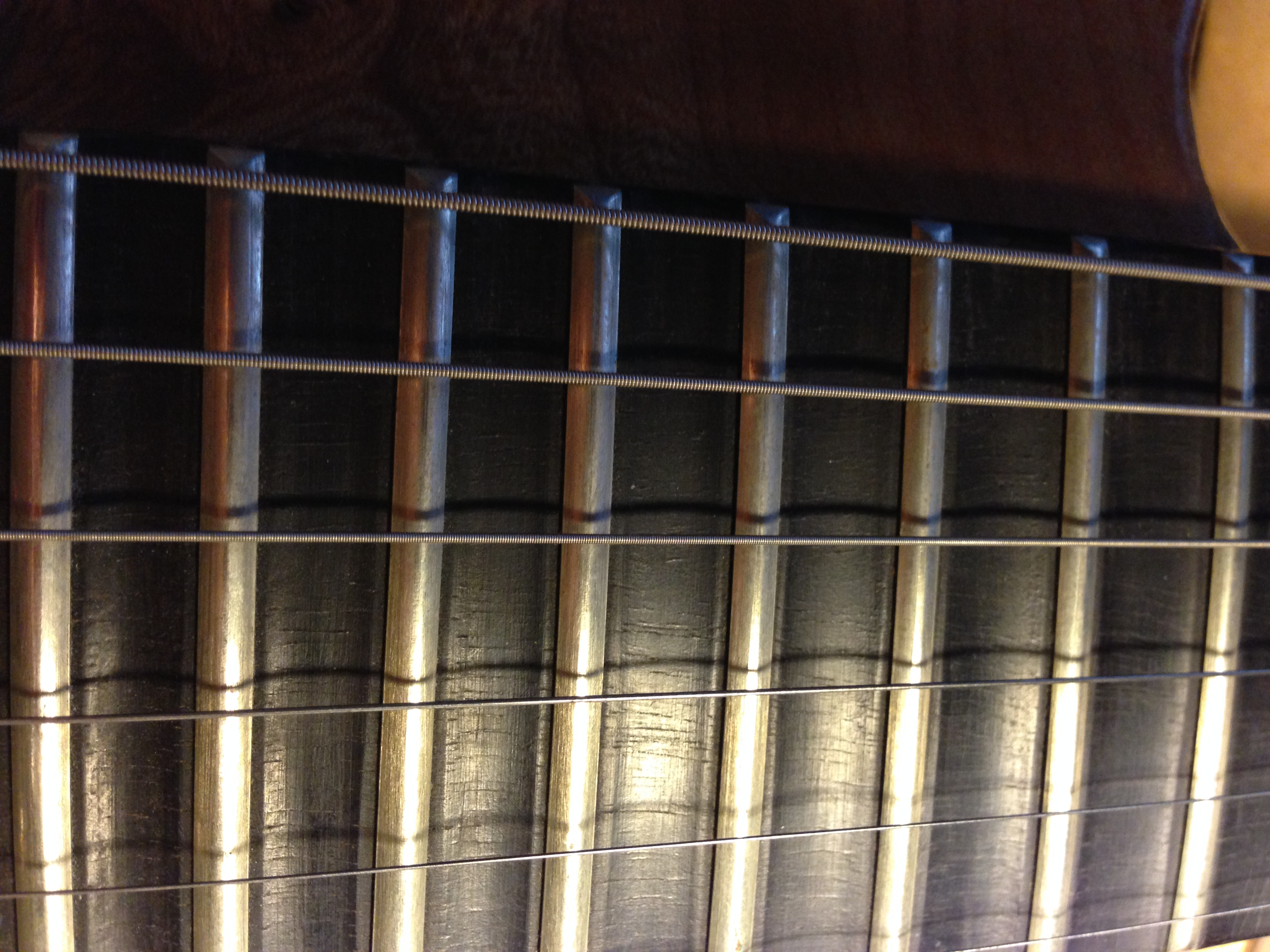 Scalloped ebony fingerboard, gradual increase from the octave to the 24th fret.